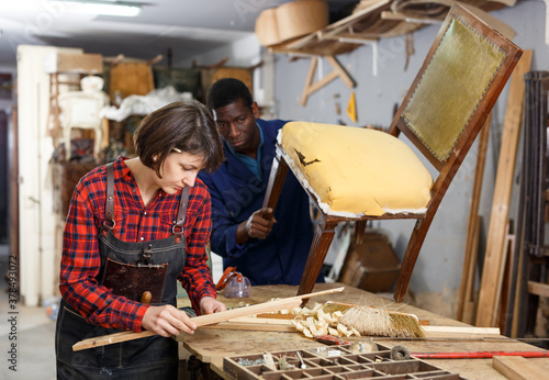 Portrait of male and female restorers working with wooden furniture in workshop Canvas