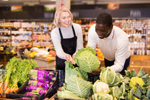 Fotomural Friendly cheerful positive glad middle aged saleswoman helping African man to ch