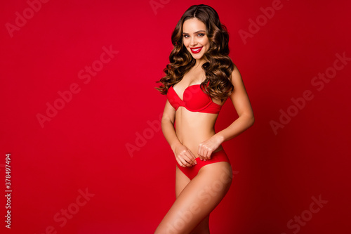 Obraz Photo of attractive beautiful seduce curly lady model advertising underwear novelty sensual slim fit body fixing soft bikini wear brassiere panties isolated red color background - fototapety do salonu