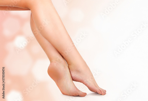 Beautiful female legs against an abstract background with sun flares and copyspace #378500476