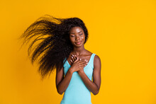 Photo Portrait Of Young Curly Brunette African American Woman Holding Two Hands On Chest With Closed Eyes Wearing Blue Dress Isolated On Vivid Yellow Colored Background