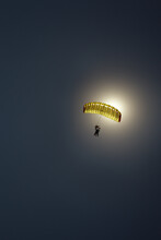 Silhouette Of A Parachute Canopy During A Tandem Jump Against The Backdrop Of A Dazzling Solar Flare And Dark Blue Sky.