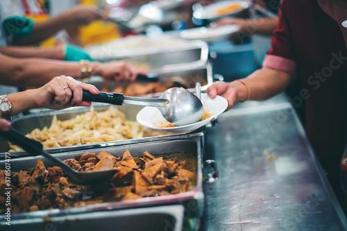 Fototapeta concept of free food serving : Volunteers serving food for poor people