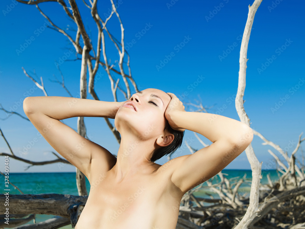 Fototapeta Beautiful nude woman on the beach with driftwood