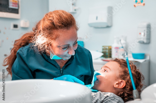 Medium shot in a medical clinic, female doctor operating a micro surgery on a young blonde caucasian boy in Rome. Health care and virus concept, mouth infection, professional sterile environment.