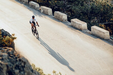 Professional Cyclist On A Mountain Road At Sunrise