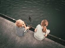 Zwei Kinder Sitzen Am Hafenbecken Und Beobachten Eine Schwimmende Ente