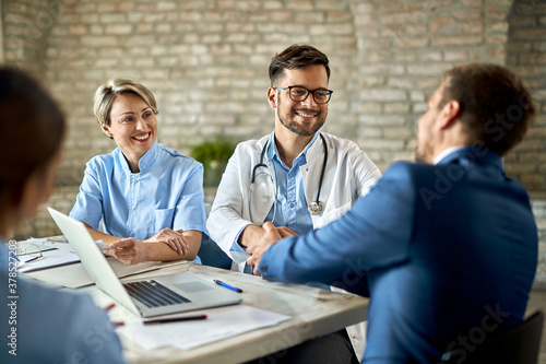 Papel de parede Happy doctor shaking hands with a businessman on a meeting in the office