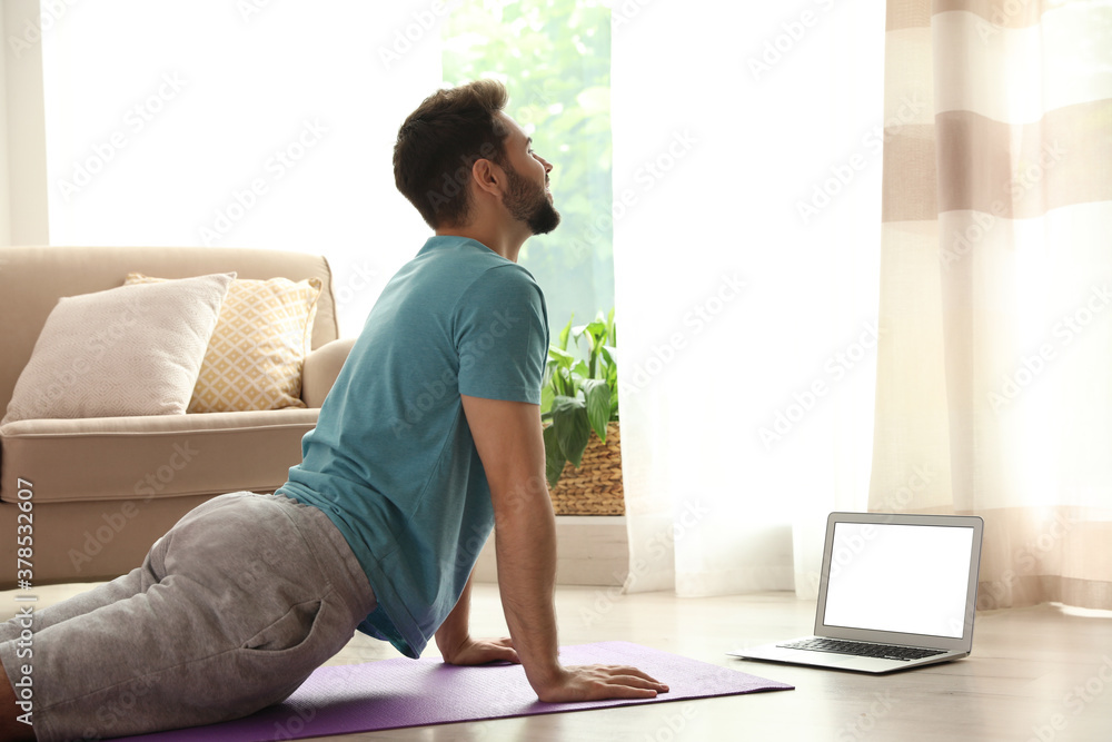 Fototapeta Man practicing yoga while watching online class at home during coronavirus pandemic. Social distancing