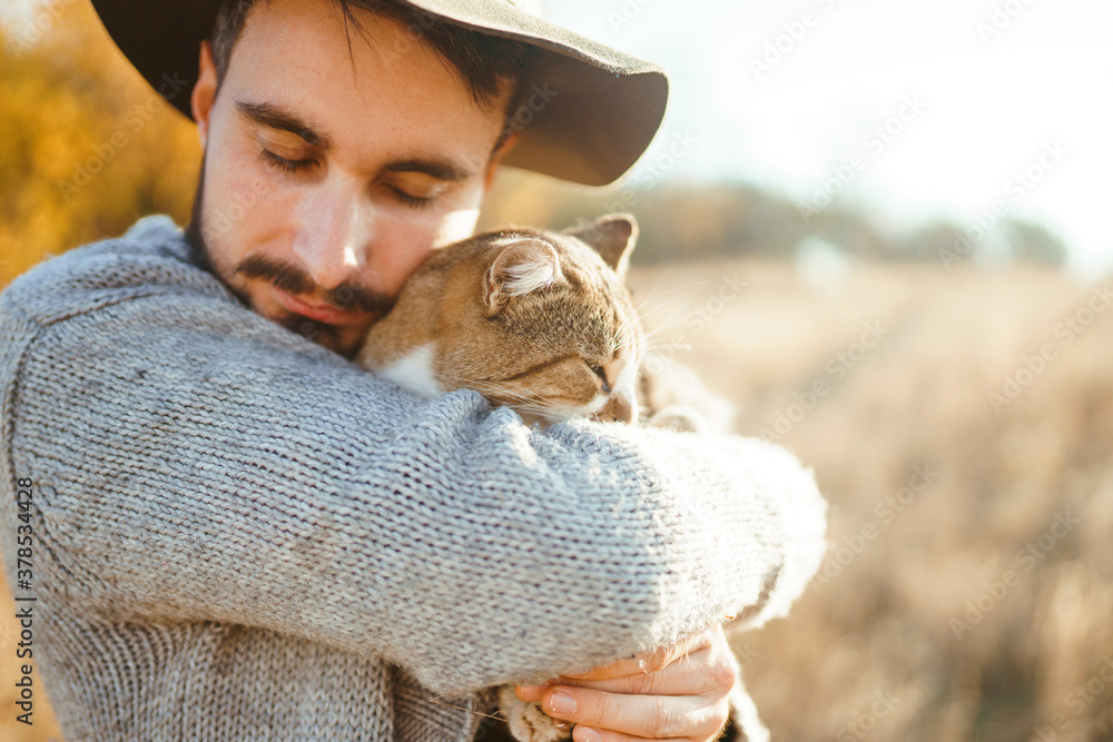 Fototapeta Portrait of stylish young hipster with a cat. Relaxing moment. Hister men is hugging a cat at sunset. The concept of youth, love and lifestyle.