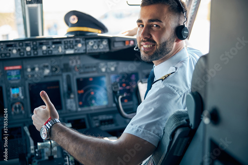 Fotografie, Obraz Handsome male posing at the camera in cabin of passenger aircraft