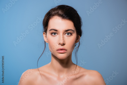 young and naked woman looking at camera isolated on blue