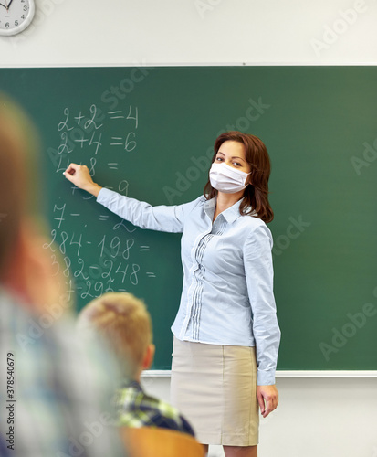 Fotografía education, school and pandemic concept - female math teacher wearing face protec
