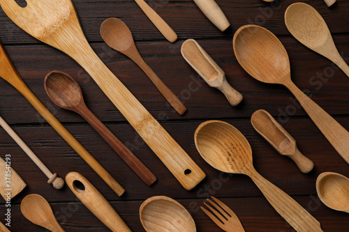 Fotografering Set of modern cooking utensils on brown wooden table, flat lay
