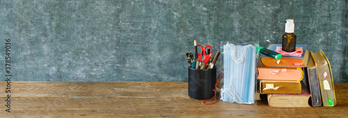 Fototapeta School supplies and COVID 19 prevention items on classroom desk with books,eyeglasses,pens on chalkboard background. Back to school during corona-virus pandemic concept. obraz