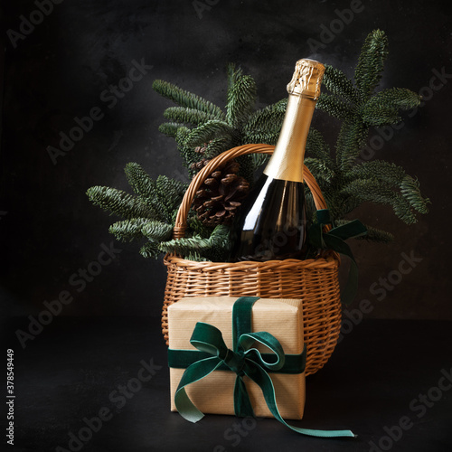 Christmas holiday gift hamper with sparkling wine and gift on black.