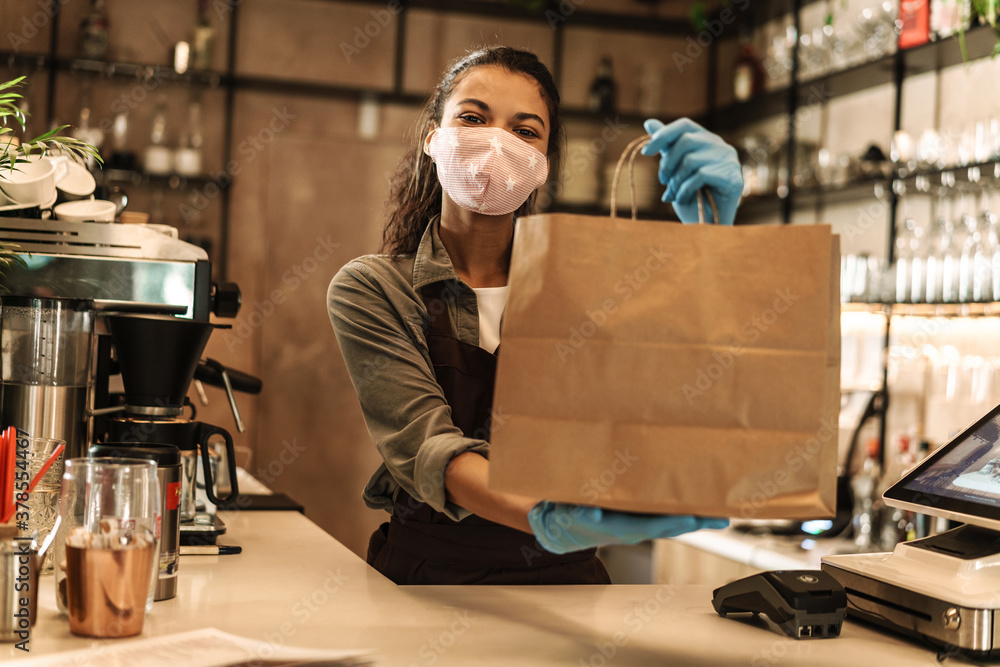 Happy woman barista wearing medical mask