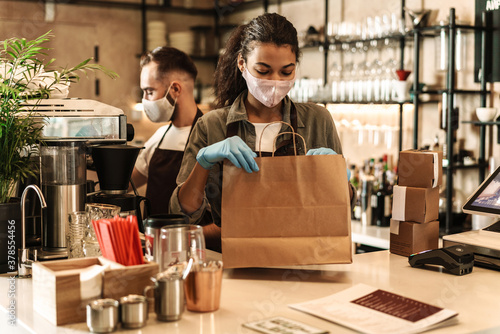 Fototapety, obrazy: Two baristas wearing medical mask serving coffee