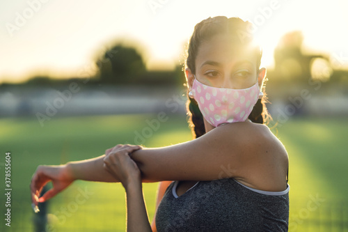 Photo Beautiful female exercising with a protective face mask in the park- COVID-19