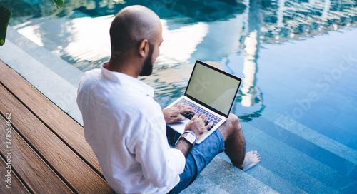 Skilled digital nomad user sitting at pool terrace in courtyard of own Indonesian villa and typing content ideas for sharing via mockup laptop with copy space area, graphic designer creating website