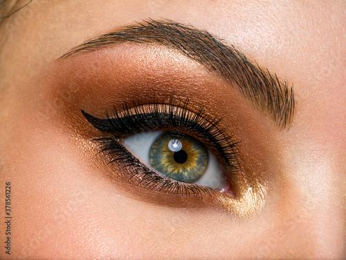 Foto Beautiful female eye with brown, shiny makeup