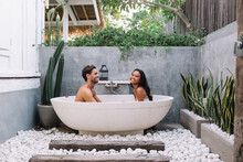 Romantica Multiracial Couple In Love Sitting In White Tub Relaxing And Enjoying Aromatherapy, Happy Male And Female Marriage Satisfied With Honeymoon Vacation On Exotic Resort With Modern Design Bath