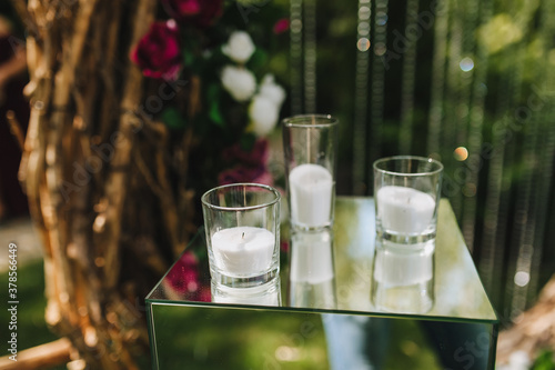 Fotografía A glass candlestick with a candle, white sand, paraffin and wax inside stands on a glass table