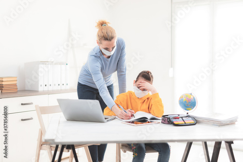 Fototapeta Child home studying education, homeschooling, with private tutor / mother with protective mask in the time of viruses, flu and seasonal pandemic. obraz
