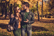 canvas print picture - Photo of positive romantic couple talk walk in autumn september town park wear backpack casual jacket