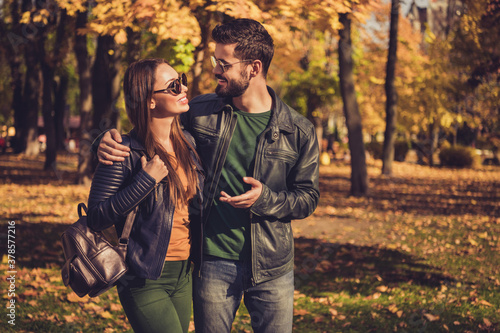 Photo of positive romantic couple talk walk in autumn september town park wear backpack casual jacket - 378577216