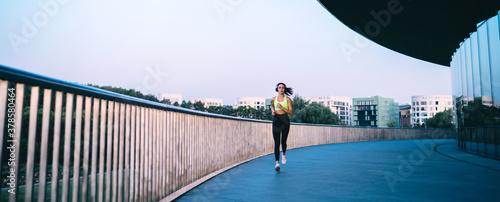 Fotografie, Obraz Active young sportswoman jogging along modern building