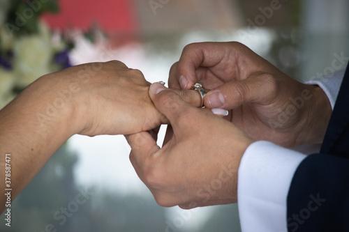 Photo El novio poniendo el anillo a su esposa en su boda