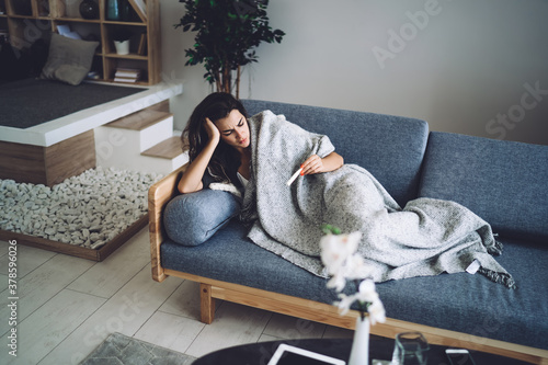 Fototapeta Young brunette lying on couch with high fever during quarantine obraz