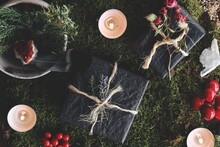 Yule (Christmas) Themed Flat Lay Of Black Gifts On Nature Forest Background. Esoteric Occult Mood Of Presents Wrapped In Black Tissue Paper, Tied With Yarn, Decorated With Flowers, Evergreens, On Moss