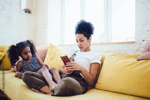 Fototapeta Mother and upset daughter sitting on sofa