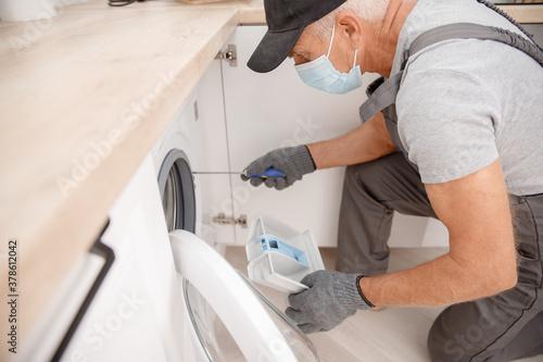 Fototapeta Working man in medical mask plumber repairs fix washing machine in kitchen. Concept service technician obraz