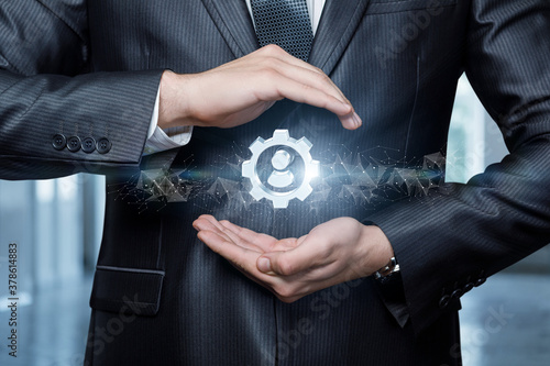 A businessman protects with a gesture a gear icon with a person . Canvas