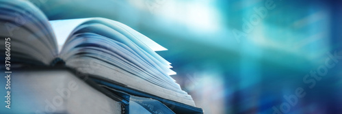 Book stack in the library and blurred bookshelf background for education Fototapeta