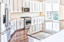 Modern Gray, Brown Kitchen Features Front Cabinets With Granite Countertops And Tile Backsplash With Island And Window