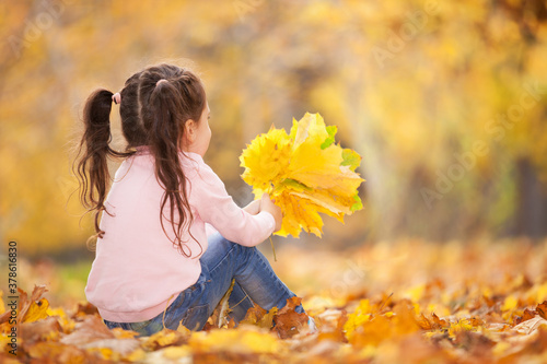Fototapeta Happy girl playing yellow leaves in the autumn park. Beauty nature scene with family outdoor lifestyle. Happy girl having fun outdoor. Happiness and harmony in childhood obraz