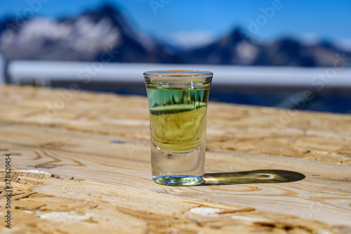 Obraz Tasting of very sweet french green strong liqueur based on many herbs, plants and flowers from Chartreuse abbey in Alpine mountains - fototapety do salonu