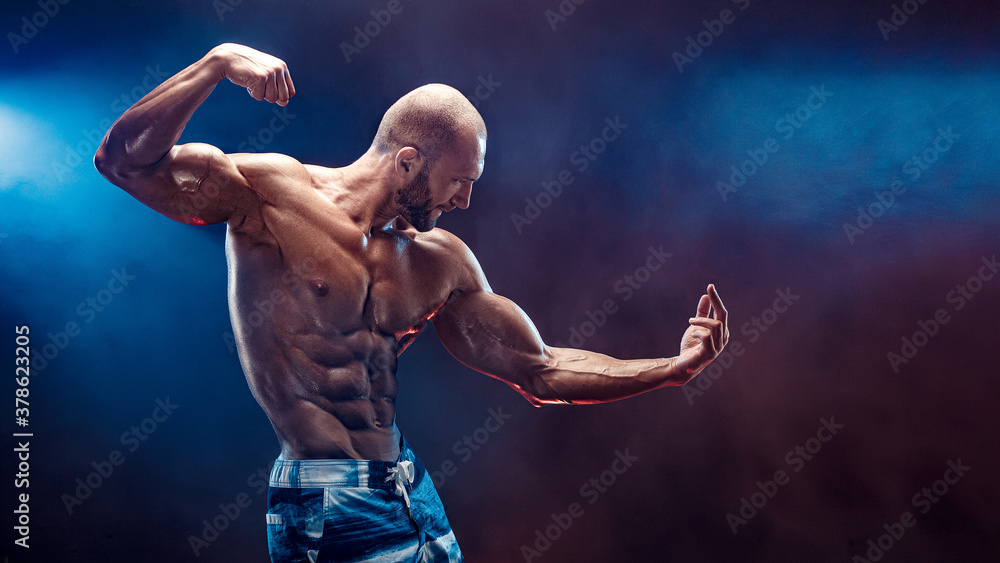 Fototapeta Handsome strong bodybuilder posing in studio on black background with smoke.