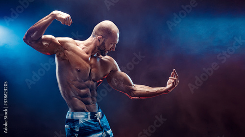 Handsome strong bodybuilder posing in studio on black background with smoke.