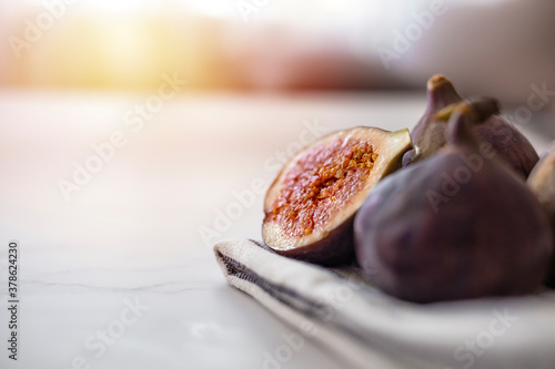 Fototapeta Fresh purple fig fruit and slices with sun background