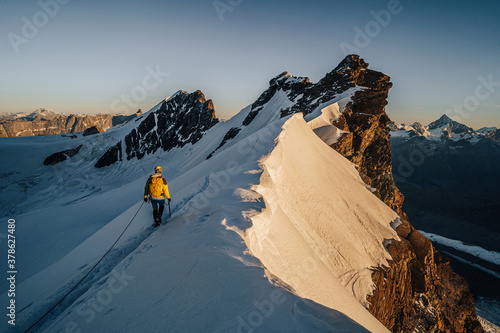 An alpinist climbing a rocky and snow mountain ridge during sunrise Canvas Print