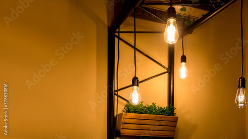 Canvas Print pendant edison bulbs in a cafe with wooden pots with green plants, vegetarian eco friendly interior style electric lighting close-up of glow details with copy space, nobody