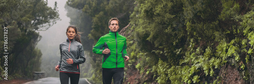 Fototapeta Runners jogging outside on wet trail running in the rain in autumn fall outdoor cold season. Panoramic of couple athletes training together. obraz