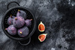 Figs in a colander, organic fruit. Black background. Top view. Copy space