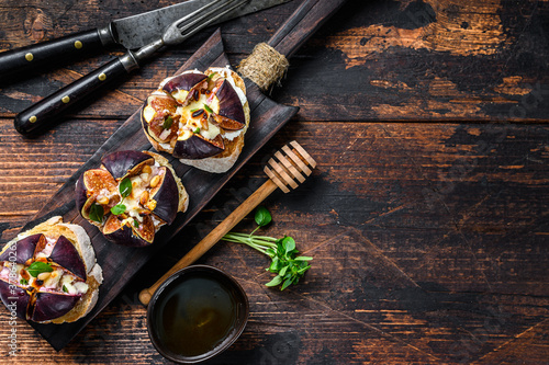 Fototapeta Sandwiches with baked figs, jam and cream cheese. Wooden background. Top view. Copy space obraz
