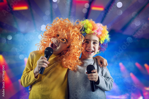 Two child sing a song with microphone and funny wig Fototapet
